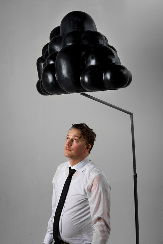 Artist Calle Holck standing under the black cloud. It is raining from the cloud and Calle is soaked.
