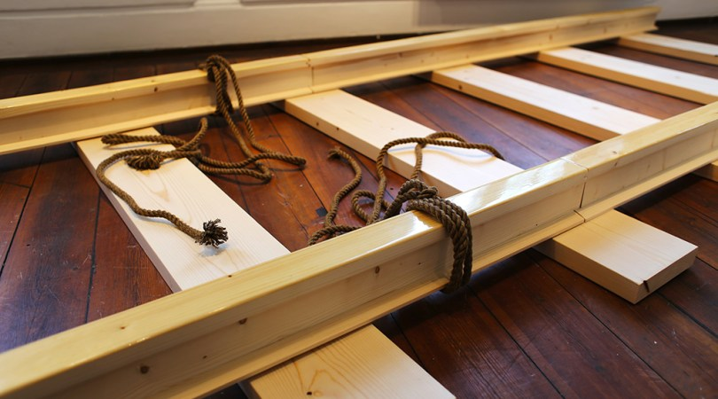A wooden part of a train lane with tied ropes to it, that has been left behind by somebody