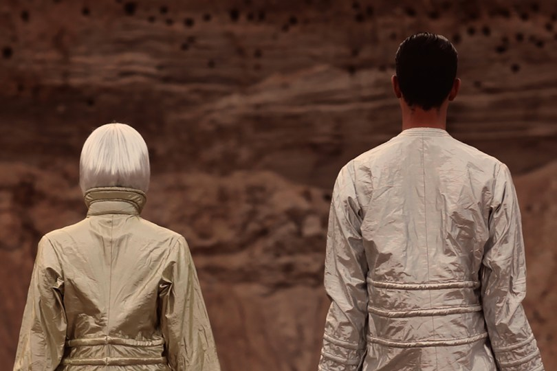 Still image from the video Twenty Happy Endings. Two people are standing with their backs towards us, with silver/alien-outfits.