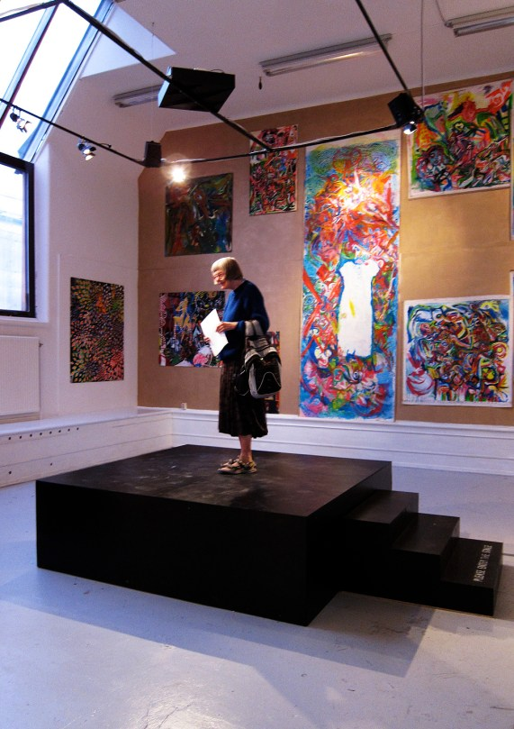 An elderly lady standing on a black small stage in the middle of the room. In the background there are art work at the walls.
