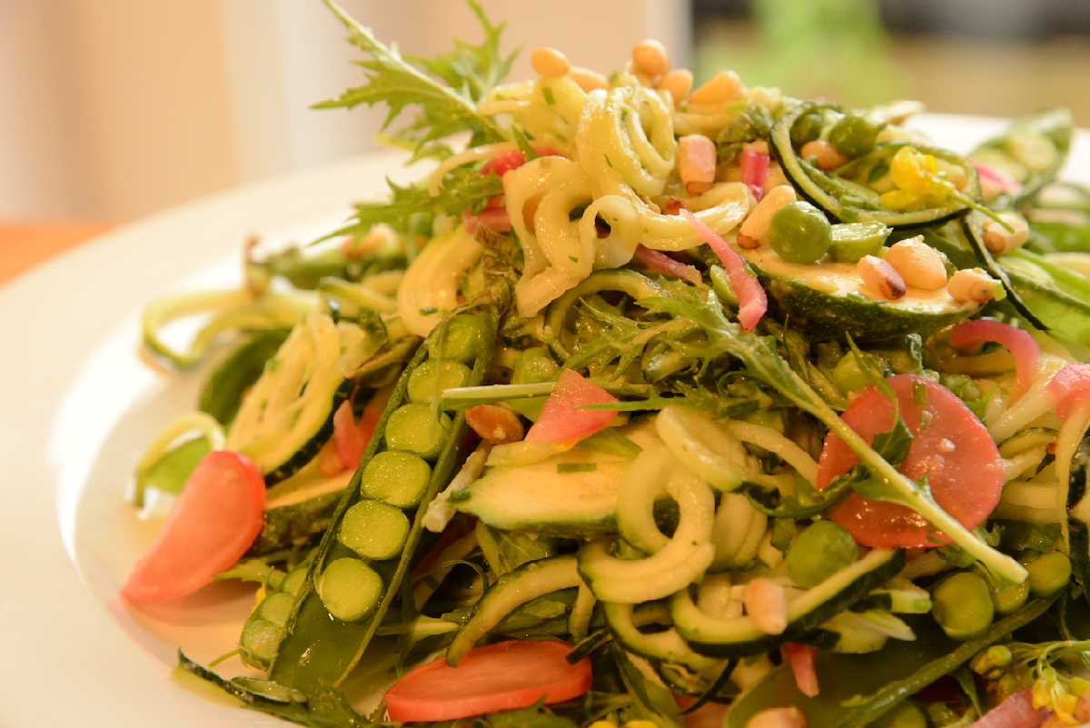 zucchini and pea salad with pink pickled rasdishes and mizen