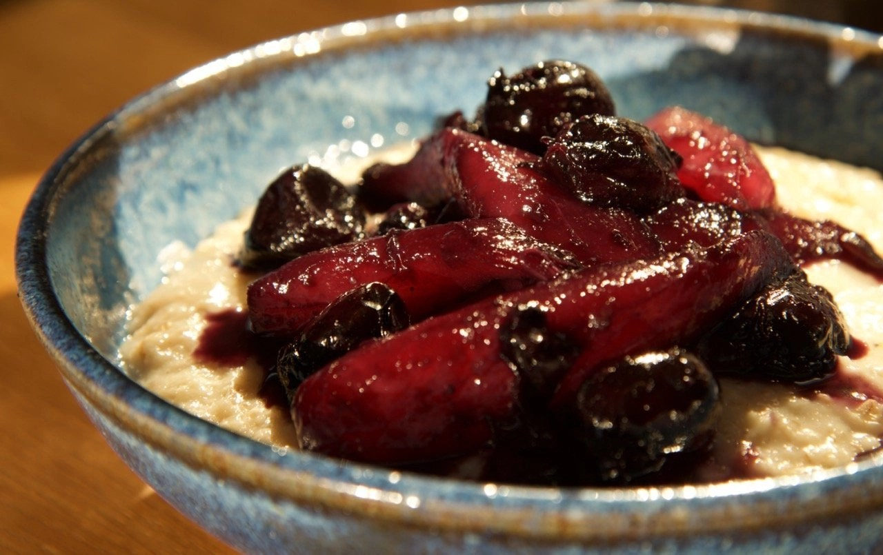 A blue pottery bowl of Pear & Cherry Compote with Creamy Porridge
