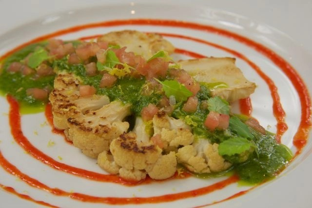 Cauliflower steak with roasted red pepper puree, chimichurri and tomato concasse