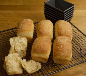 6 mini bread loaves cooling a baking rack.