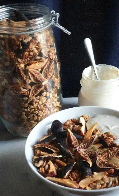 A bowl and jar of Autumn Foragers Granola with plant-based yoghurt on a marble bench