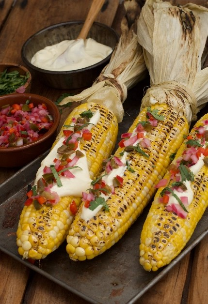 3 Barbecued corn cobs garnished with mayo, jalapeño salas and chopped coriander