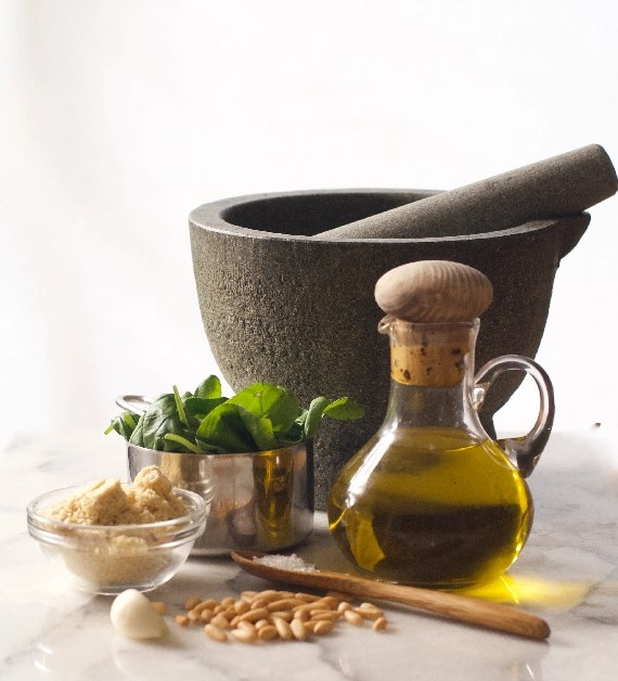Marble bench with pestle and mortar and the fresh ingredients for plant-based pesto