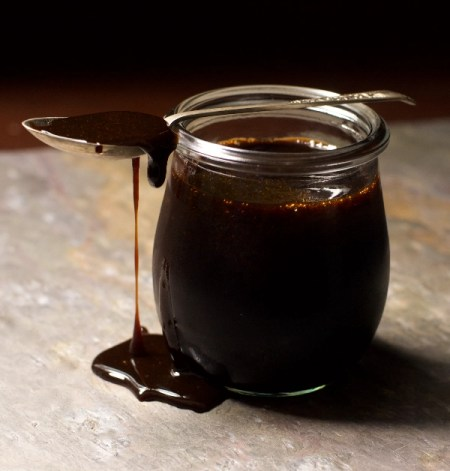 A jar of Date syrup with a drizzle and teaspoon
