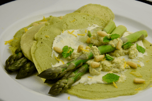 A plate with green sorrel crepes, cashew cream, asparagus with pine nuts and mint