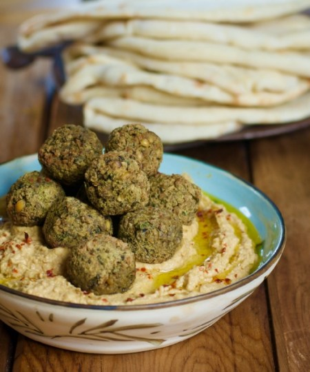A bowl of falafel on hummus with pitta
