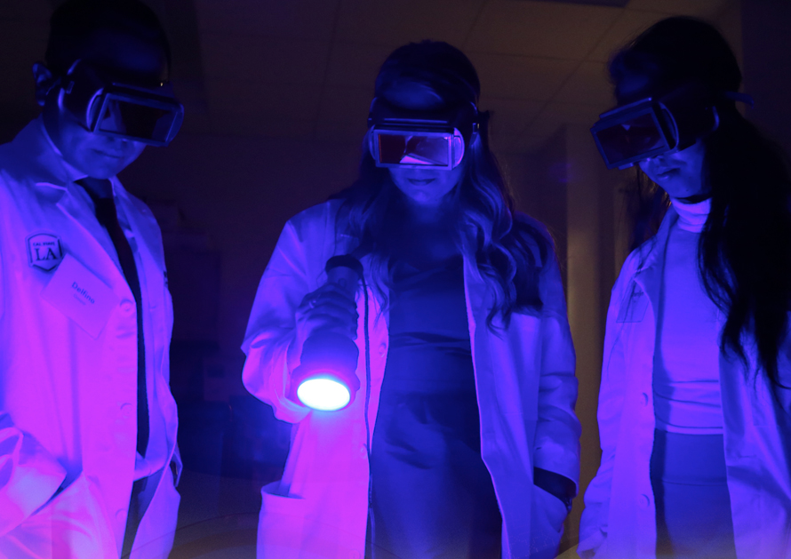 Students demonstrate Luminol tests that reveal previously hidden traces of blood at Hertzberg-Davis Forensic Science Center celebration.