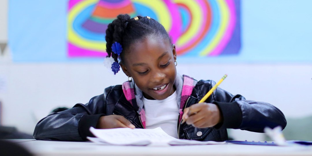 Student smiling and working on classwork at Crete Academy.
