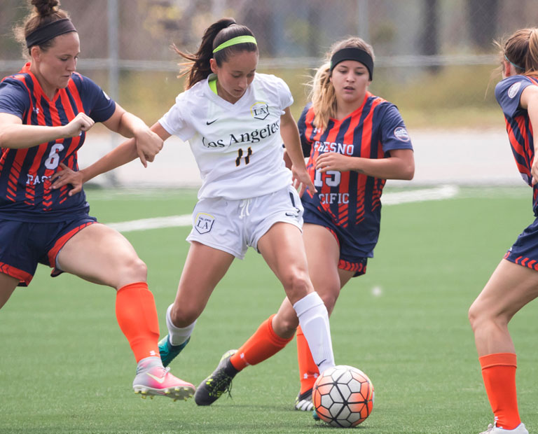 Paulina Chaidez splits three Fresno Pacific soccer players.