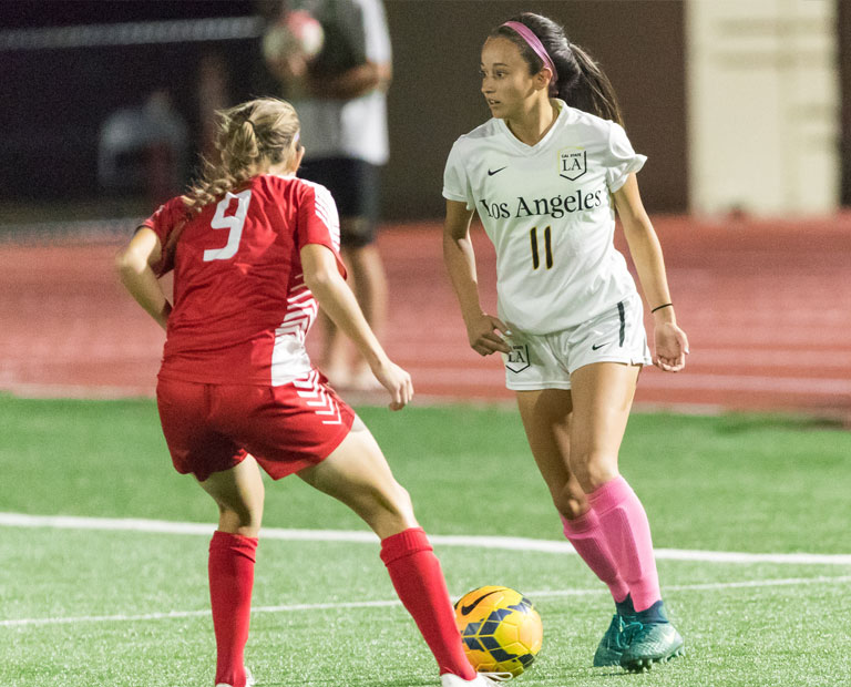Paulina Chaidez looks for teammates up the field while dribbling the ball.