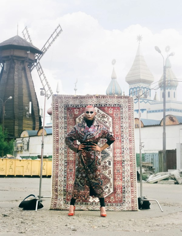 Lorina Rey, a Russian drag queen, standing in front of a rug.
