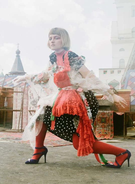 Dasha, artist and teacher, posing wearing red paired with a white polka dot dress.