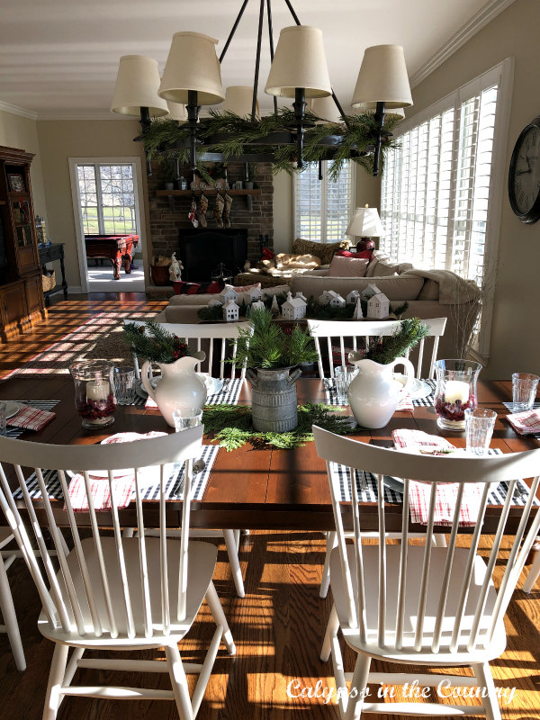 Farm table with white chairs in open concept kitchen