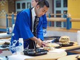 Tomo cooking an okonomiyaki
