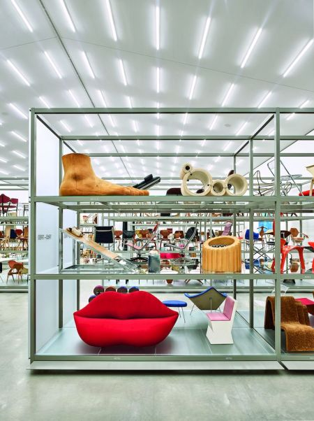 A shelf in a storage area a the Vitra Schaudepot hold iconic furniture designs, including a red chair that looks like lips.