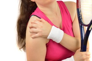 woman tennis player with a shoulder injury isolated over white background