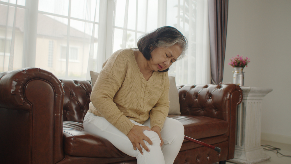 woman sitting on sofa holding knee due to pain