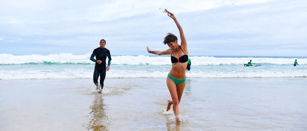 Camino Surfcamp Galicien Mel in Bikini running towards Camera with Pete in the Background