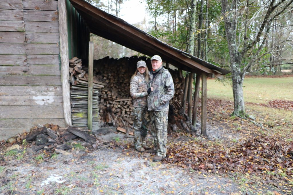 rustic woodshed  backdrop and   hunting couple