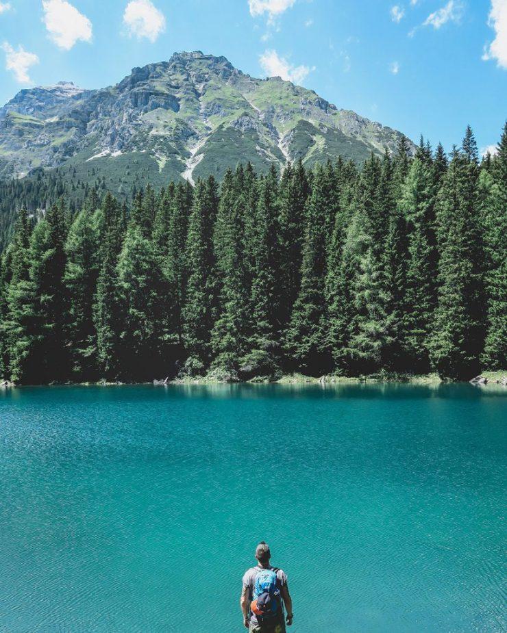 Ein Mann steht vor einem See in der Nähe von Bozen, mit Blick auf die Berge