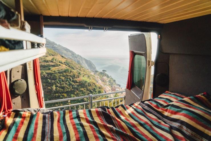 Durch die offene Heckklappe eines Campers ist bergige Landschaft an der Küste zu sehen.