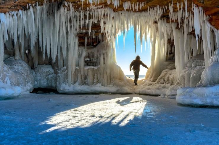 Eine Person in einer, von riesigen Eiszapfen verzierten, Höhle.
