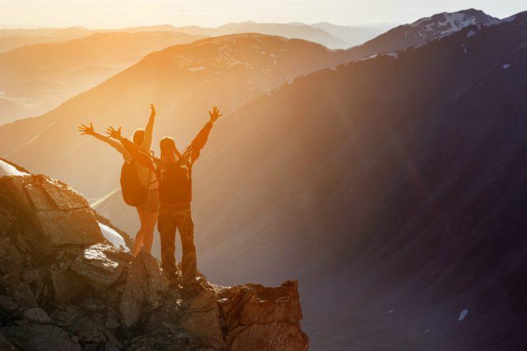 Zwei Personen stehen auf einer Klippe im Gebirge.