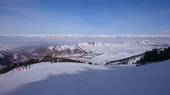 Looking back down towards Karakol with the mountainous border with kyrgyzstan in the background and the start of Issy Kul far left. Les Menuires chairlift also visible.