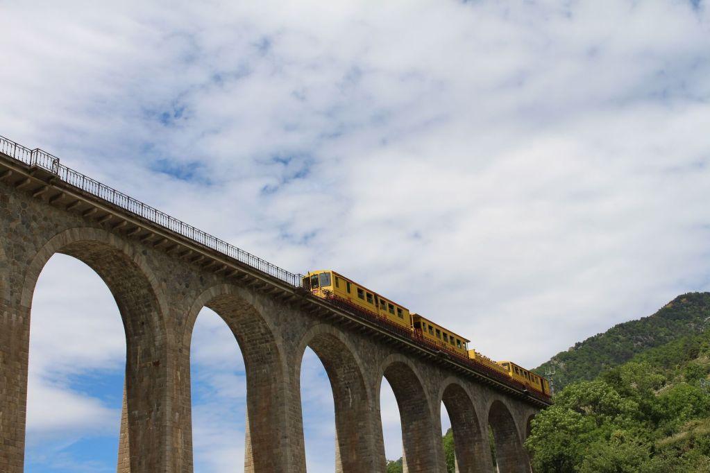 train_jaune_sur_pont_en_pierre_depart_de_villefranche_de_conflent