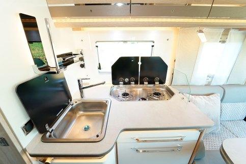 Le nouveau revêtement stratifié du plan de travail de la cuisine et de la table du salon est plus en adéquation avec les standards de la déco domestique.