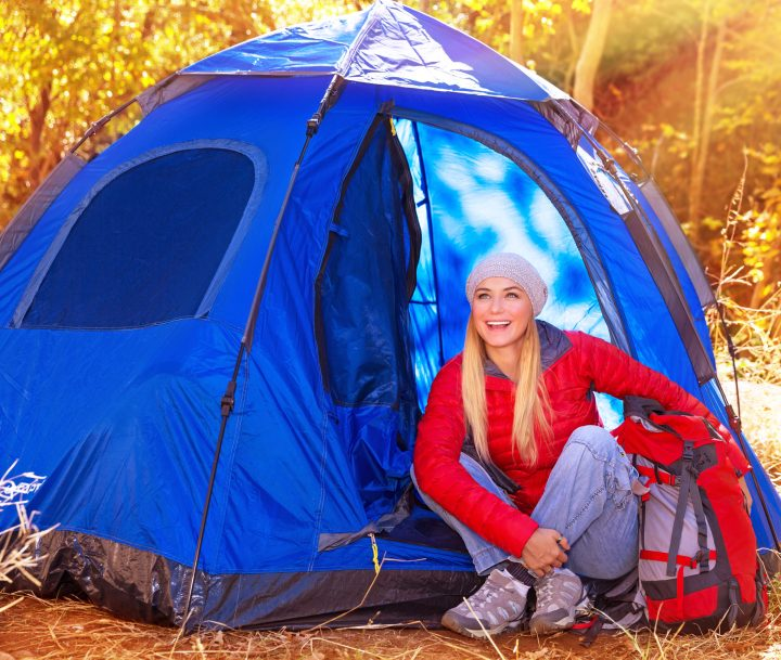 Happy Glam woman by her tent.