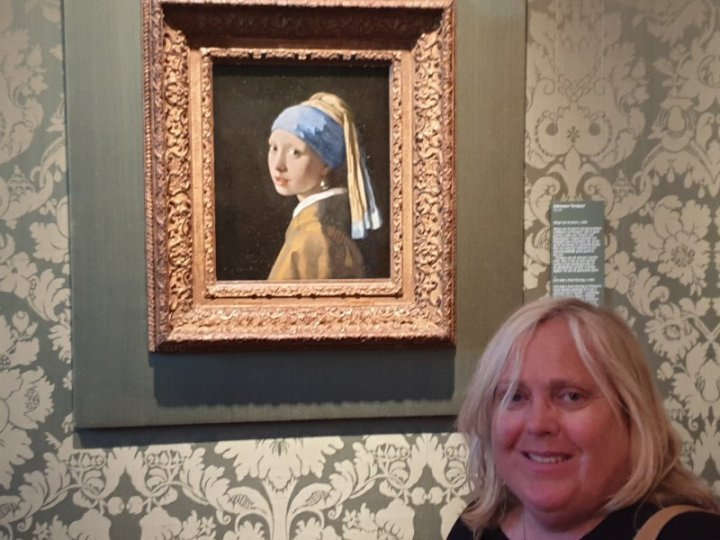 In front of the original painting of the Girl with the Pearl Earring at the Mauritshuis museum
