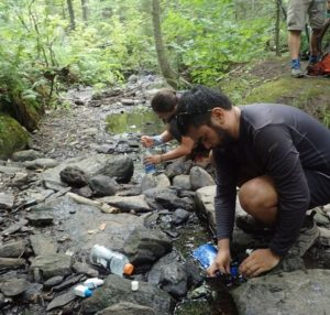 Backpacking Water Strategy: Hikers filter water and refill their bottles along the Appalachian Trail.
