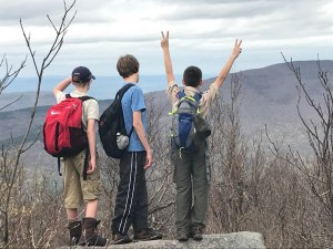 Three scouts from Rochelle Park Troop 114 celebrate their final peak for the day, Thomas Cole.