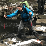 A hiker uses trekking poles to carefully descend a slippery trail.