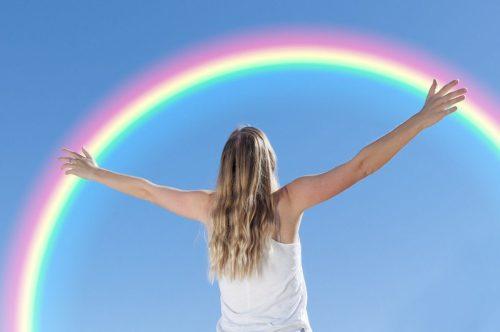 femme les bras ouverts face à un magnifique arc-en-ciel