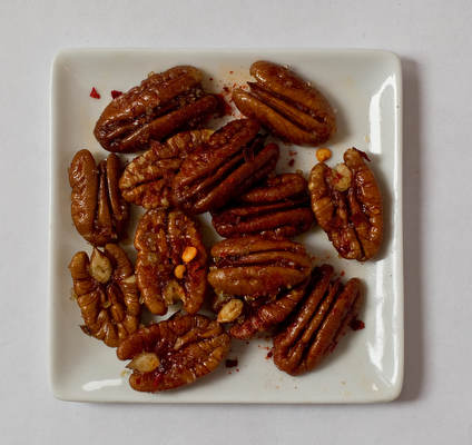 Sweet and spicy pecans. Preheat oven to 325F. Toss pecans, walnuts and/or almonds with a drizzle of olive oil, coarse salt, chili pepper flakes, cumin and brown sugar. Spread nuts in a single layer on a parchment paper-lined baking sheet and roast for 15 to 20 minutes or until lightly toasted and glazed.
