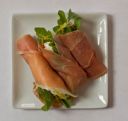 Prosciutto-ricotta roulades. Combine ricotta cheese with grated Parmesan or pecorino cheese, freshly ground black pepper and finely grated lemon zest. Lay out slices of prosciutto, spread with a spoonful of ricotta mixture and scatter with arugula leaves, then roll up.