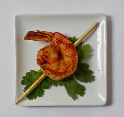 Spicy Thai jumbo shrimp. Sauté finely chopped onion in vegetable oil with Thai red curry paste. Add large, shelled shrimp and sauté until pink. Drizzle with freshly squeezed lime juice and skewer.