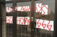 [A photograph of the front of the Ottawa Muslim Association mosque, showing crude graffiti spraypainted in red. The graffiti is 'FUCK ALLAH', then a swastika, then 'GO HOME', then '666'.]