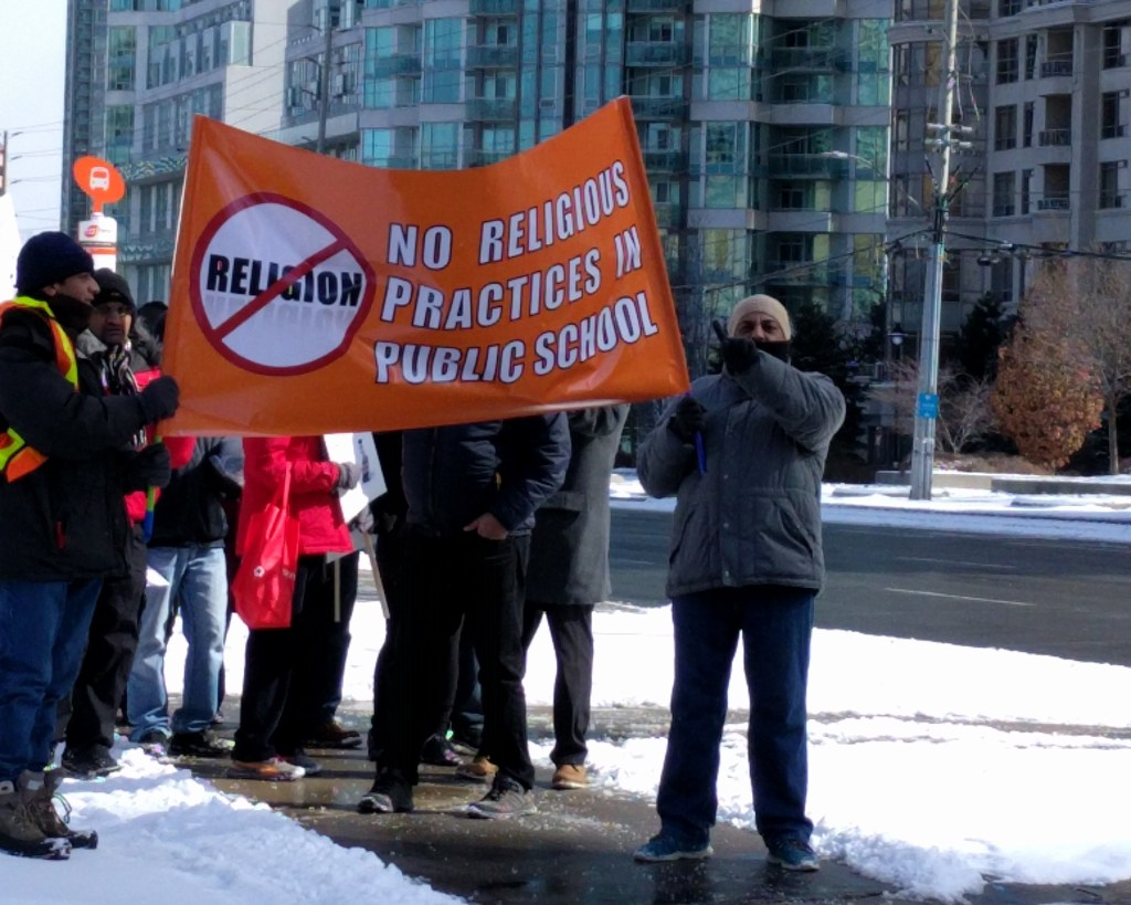[Photo of protesters marching in Mississauga, with a large sign reading: No religious practices in public school.]