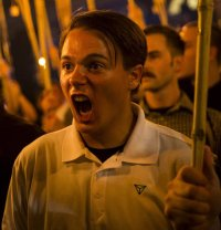 [Peter Cvjetanovic at the Charlottesville alt-right rally, holding a torch, wearing an Identity Evropa shirt, screaming.]