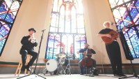"""[Screenshot from """"Mythical Riddles"""" video, showing musicians James Fry (acoustic guitar, vocals), Anton Fierce (trumpet), Eli Bender (cello), and Dan Beer (drums) performing with stained glass windows as a backdrop at Christchurch Cathedral in Victoria, British Columbia.]"""