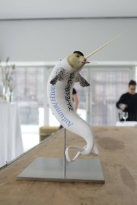 """[A photo of a statuette of a bizarre creature that looks like a white narwhal with a fairly anthropomorphic, flesh-coloured face. It is sucking on a lollipop, wearing a black beret, and it has the words """"Autumn/Hiver"""" in decorative text along its side. Its tail fin is shaped like an infinity symbol.]"""