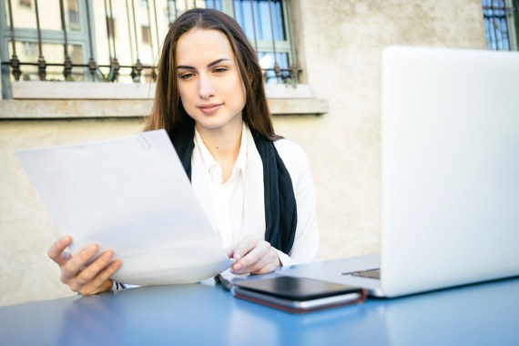 Cheerful-Businesswoman-Reading-Documents-000061693608_Medium