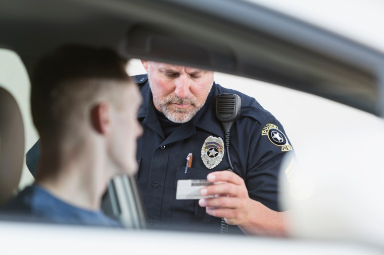Serious police officer pulling over a young driver for a traffic violation, checks his identification. Focus on the policeman.